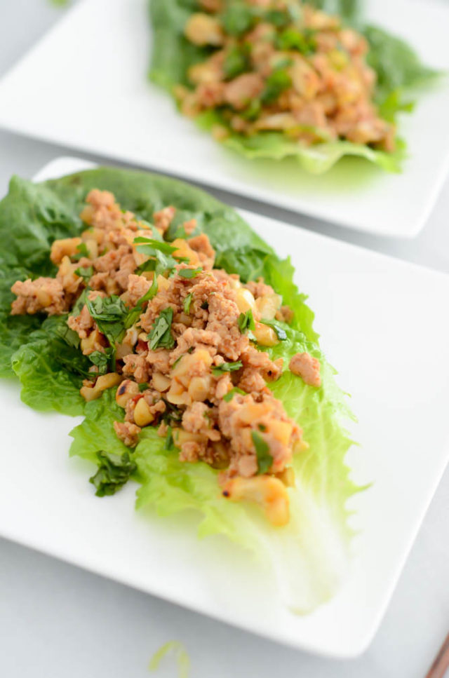 Two white plates loaded with lettuce wraps.