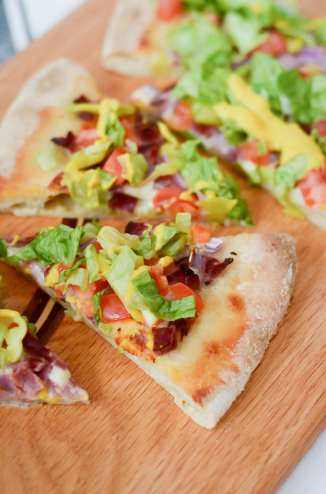 A close up view of a few pieces of Pastrami Pizza on a wooden cutting board.