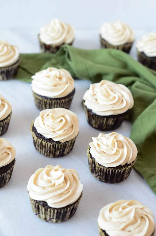 Frosted chocolate cupcakes on a white marble tabletop with a green napkin.