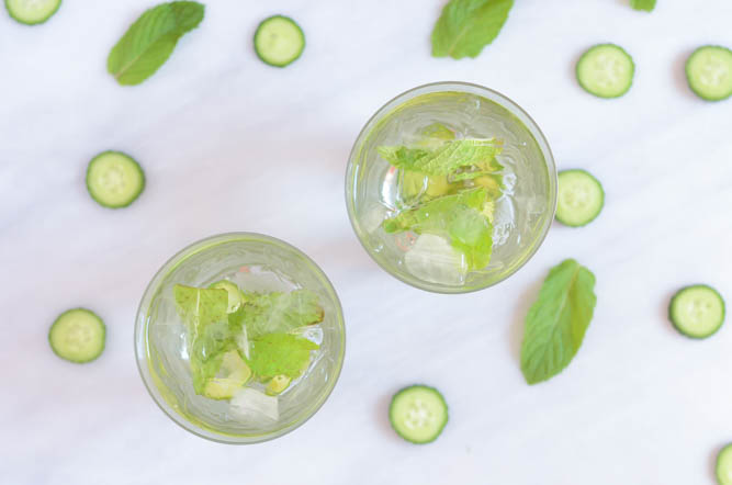An overhead shot of two cucumber mint spritzers surrounded by slices of fresh cucumber and mint leaves.
