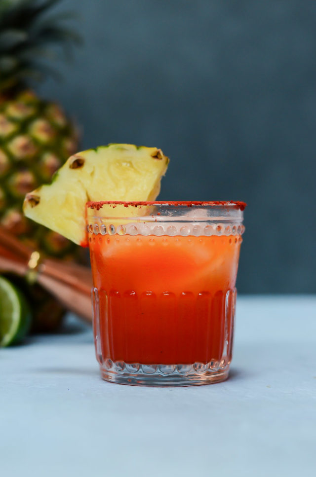 A single Li Hing Pineapple Margarita garnished with a pineapple wedge.