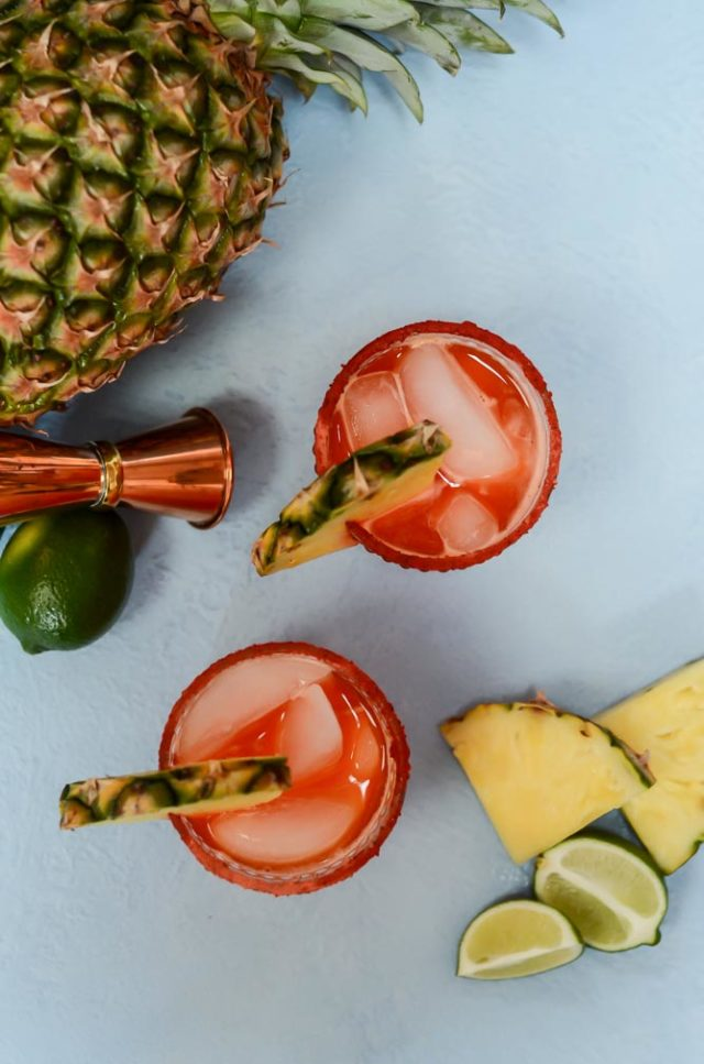 An overhead shot of two bright red Li Hing Pineapple Margaritas, surrounded by more fresh pineapple, lime and a cocktail jigger.