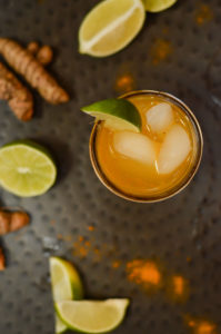 An overhead shot of a turmeric cocktail garnished with a lime and served on a black metal tray.