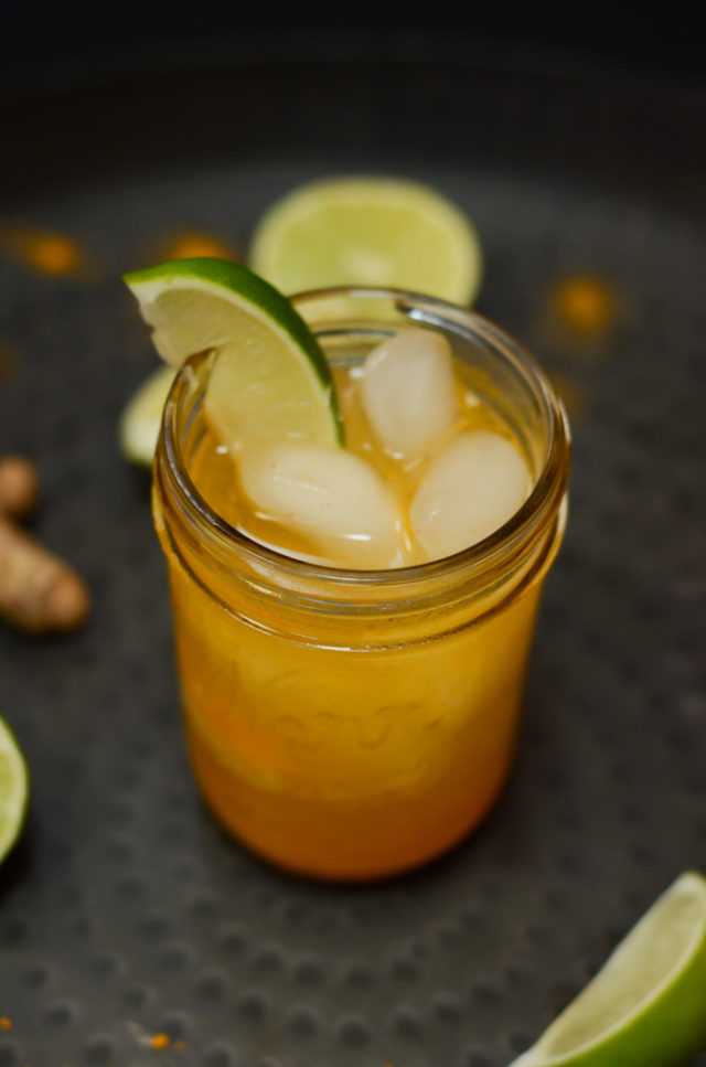 A shot of a Turmeric Gin and Ginger Cocktail in a Mason jar garnished with a fresh lime wedge.
