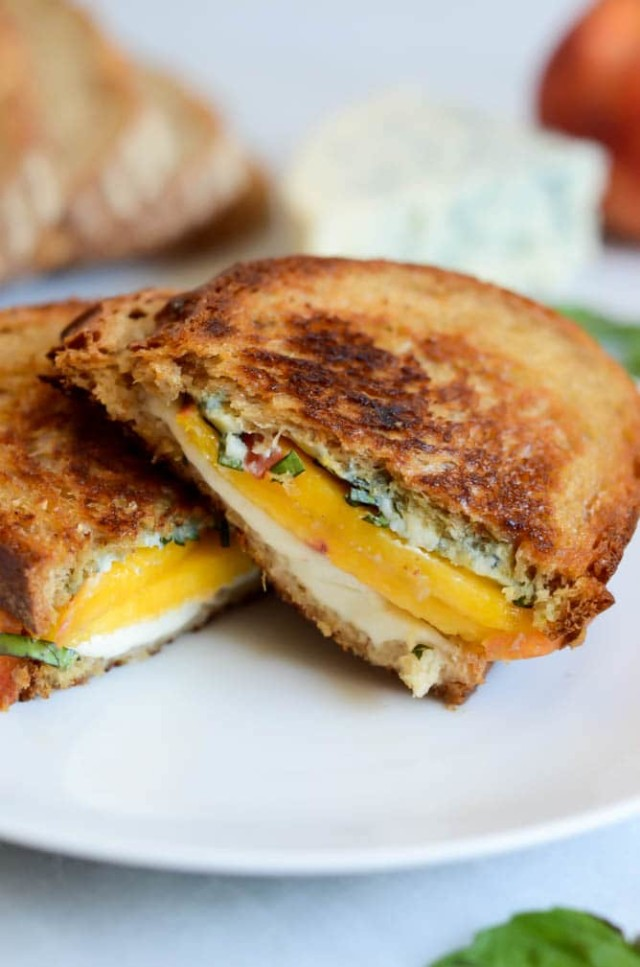 A Honey, Peach and Basil Two-Cheese Grilled Cheese cut in half and placed on a white plate.