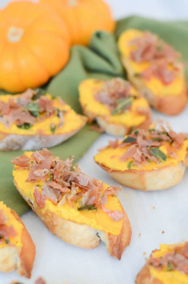 A closeup of assembled butternut squash crostini topped with crispy prosciutto and sage.