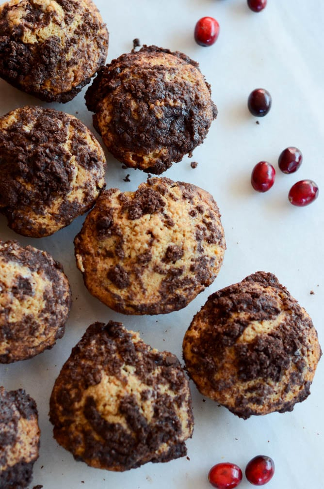 Overhead shot of cranberry chocolate chunk muffins on white countertop.