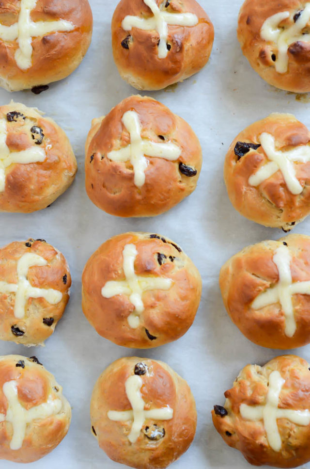 An overhead shot of a batch of Hot Cross Buns with icing.