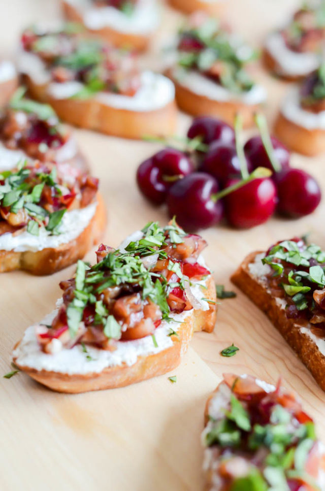 A close-up shot of a piece of Herbed Cherry and Ricotta Crostini. You won't be able to stop eating these!