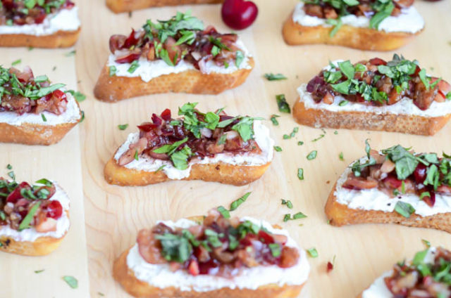 Rows of Herbed Cherry and Ricotta Crostini ready to be consumed at your next cookout!