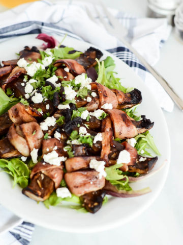 A large serving platter of Bacon-Wrapped Portobello Mushrooms with Goat Cheese over a bed of mixed greens.
