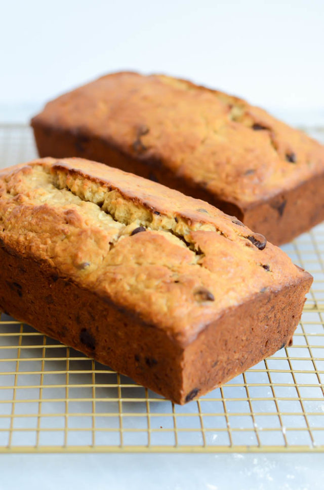 Two freshly baked loaves of Coconut Chocolate Chip Banana Bread cooling on their racks.