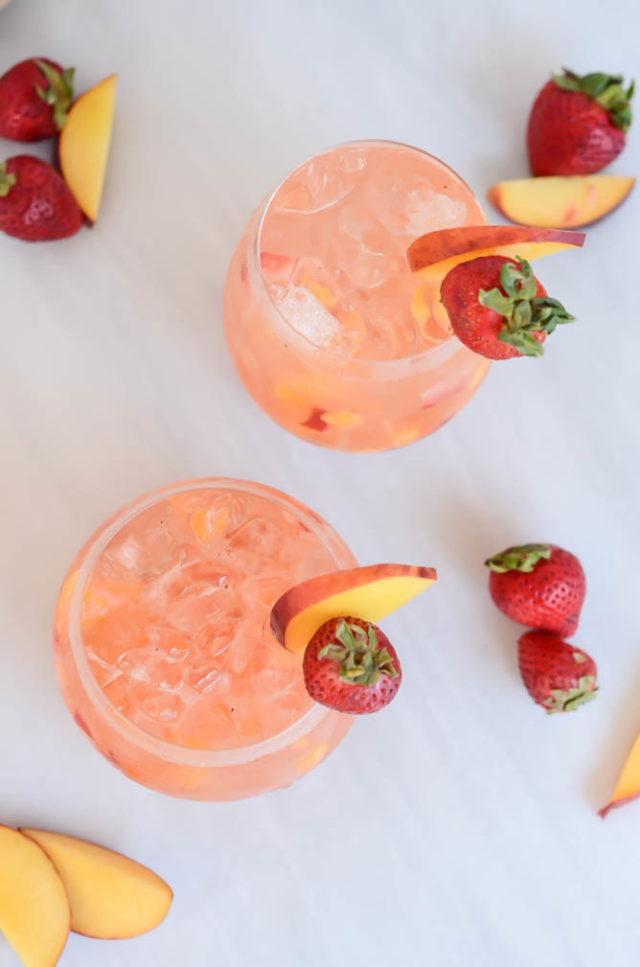 An overhead shot of two glasses of the refreshing Ginger Strawberry Peach Smash.