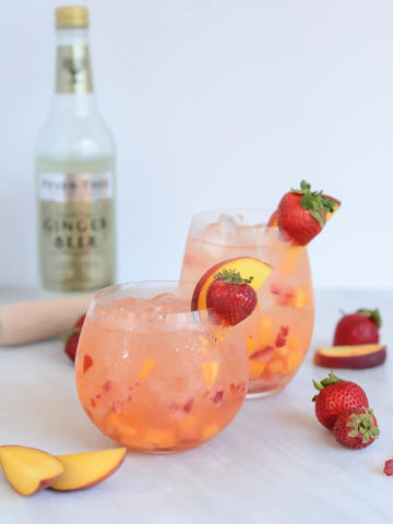Two chilled glasses of a refreshing Ginger Strawberry Peach Smash from CaliGirlCooking.com.