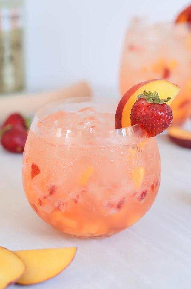 A close-up shot of a Ginger Strawberry Peach Smash from CaliGirlCooking.com.