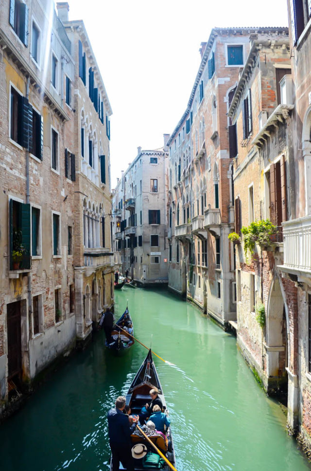 A gondola travels up one of the many canals of Venice.