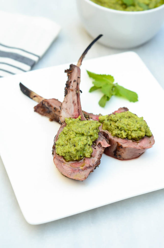 Lollipops of Herb Crusted Rack of Lamb are graced with a hearty dollop of Mint Pea Pesto.