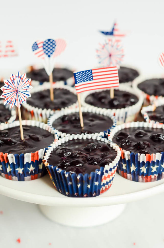 A big cake stand full of Patriotic Cheesecake Bites. The perfect dessert to celebrate the 4th of July!