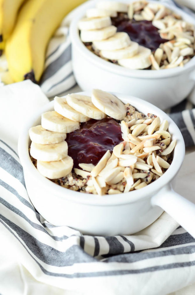 Two PB&J Quinoa Breakfast Bowls complete with toppings, sitting atop striped dish towels.