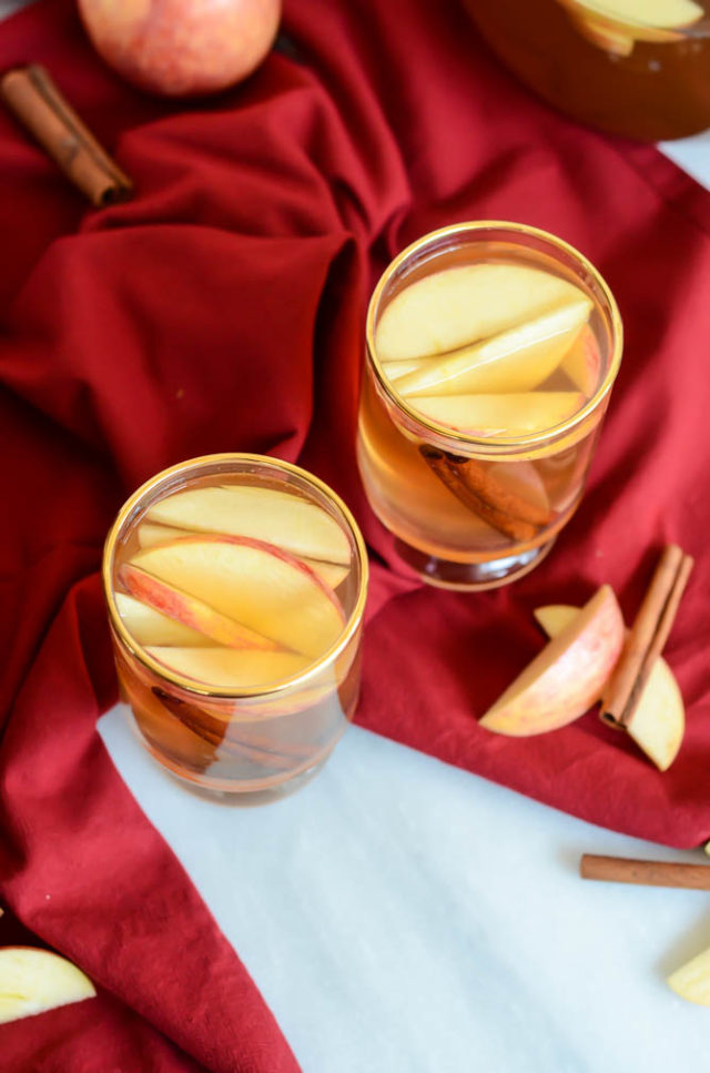 An overhead shot of two glasses of spiced apple cider.
