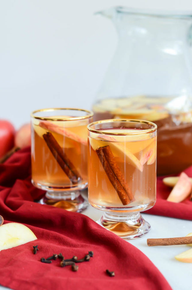 Two glasses of slow cooker spiced apple cider with a pitcher behind them.
