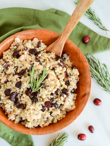 A bowl of Cranberry, White Bean and Grain Salad surrounded by a green linen napkin and fresh cranberries.