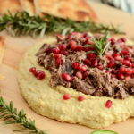 This Loaded Mediterranean Hummus Board features slow-cooked pulled lamb, pomegranate arils and refreshing sliced cucumber to make the perfect healthy appetizer for your next get-together!