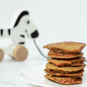 A stack of Healthy Carrot Cake Pancakes with a wooden zebra pull toy behind it.