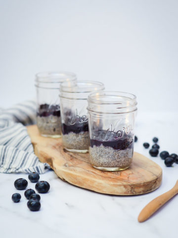 Three jars of Oat Milk Chia Pudding topped with Blueberry Orange Compote on a wooden serving plank.