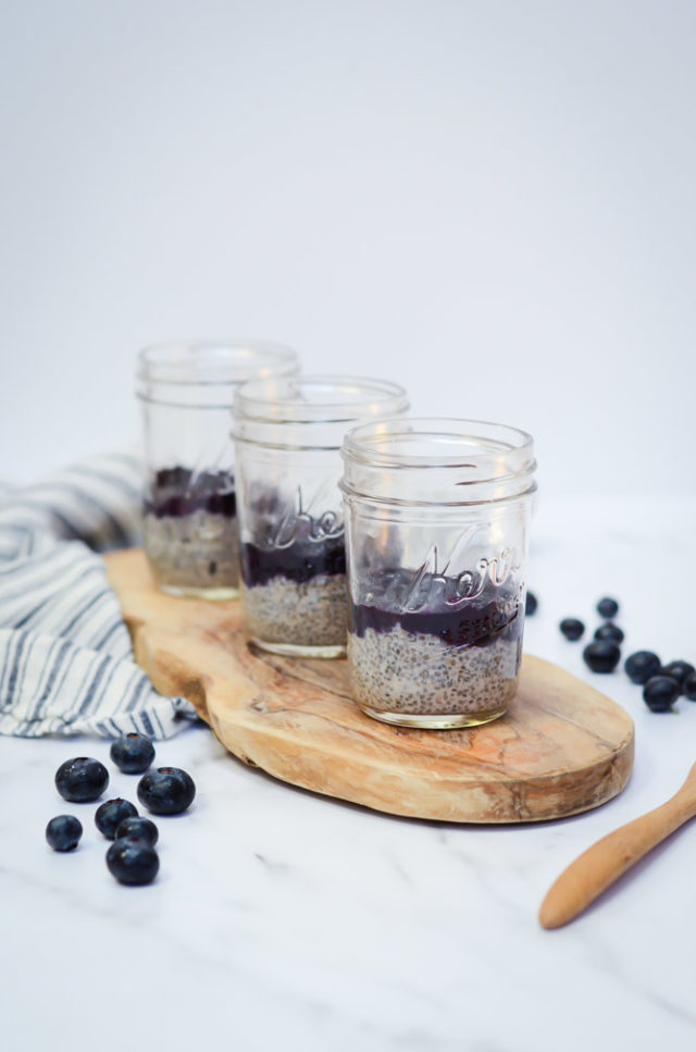 Three jars of Oat Milk Chia Pudding with Blueberry Orange Compote lined up on a rustic wood serving tray, surrounded by fresh blueberries.