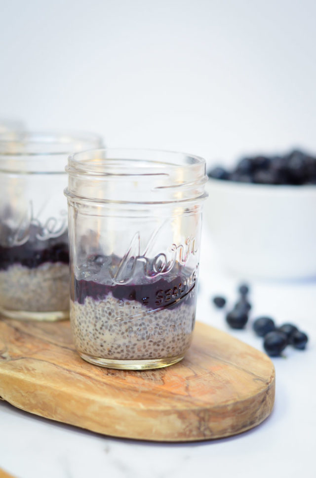 A close-up shot of a jar of Oat Milk Chia Pudding with Blueberry Orange Compote with a bowl of blueberries in the background.