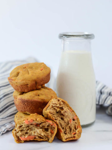 A stack of pumpkin carrot muffins, plus one broken in half, in front of a small carafe of milk.
