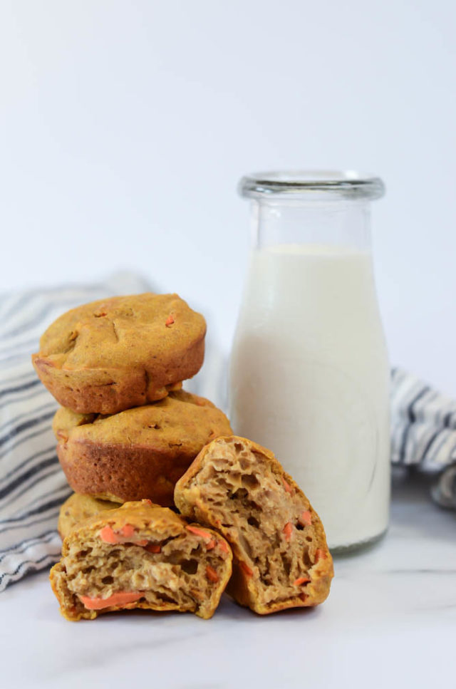 A tall stack of Super Simple Pumpkin Carrot Muffins leaning against a carafe of milk.
