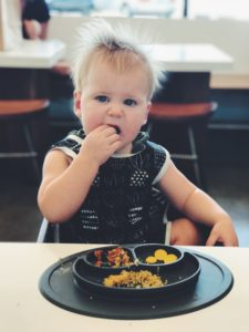 A toddler enjoying a plate full of healthy food thanks to a healthy meal prep plan.