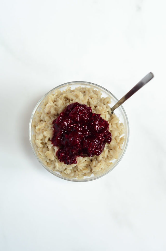 A clear glass dish of oatmeal topped with berry compote.