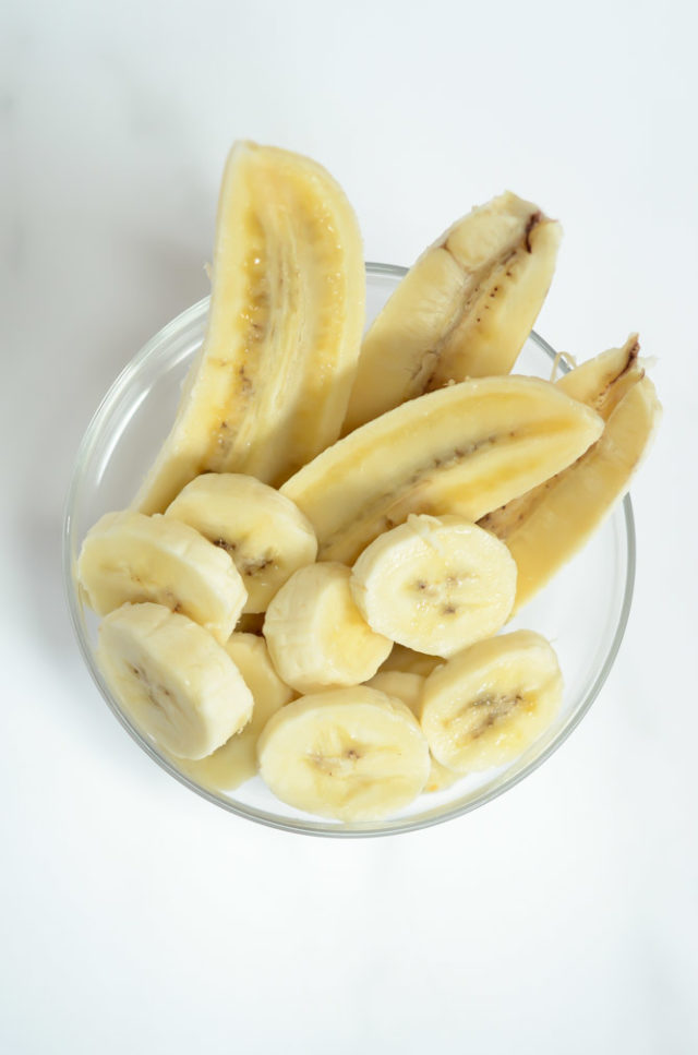 A clear glass dish full of sliced banana.