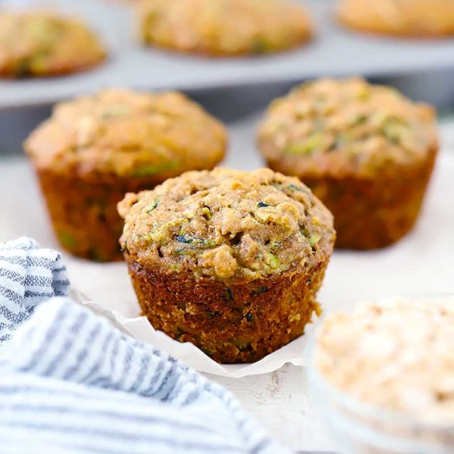 Three Healthy Zucchini Muffins freshly pulled out of the pan.