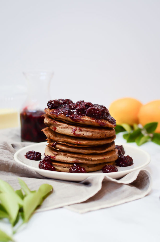 A stack of Lemon Vanilla Buckwheat Pancakes topped with a homemade blackberry syrup.