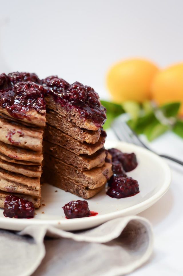 A stack of Lemon Vanilla Buckwheat Pancakes with Blackberry Syrup with a big wedge cut out of them.