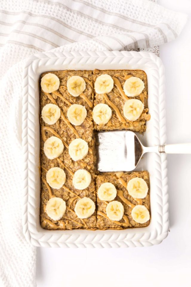 A pan of fresh baked Peanut Butter Banana Baked Oatmeal with a piece cut out of it.