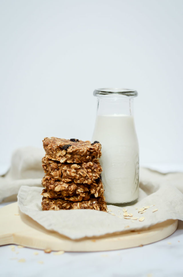 Four Peanut Butter Banana Breakfast Cookies stacked alongside a carafe of milk.