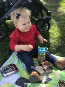 A happy toddler enjoying a lunch picnic on the grass. Picnics are a great thing to plan into your baby or toddler's meal plan!