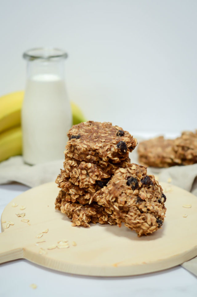 A stack of Toddler-Approved Peanut Butter Banana Breakfast Cookies with a carafe of milk and bunch of bananas in the background.