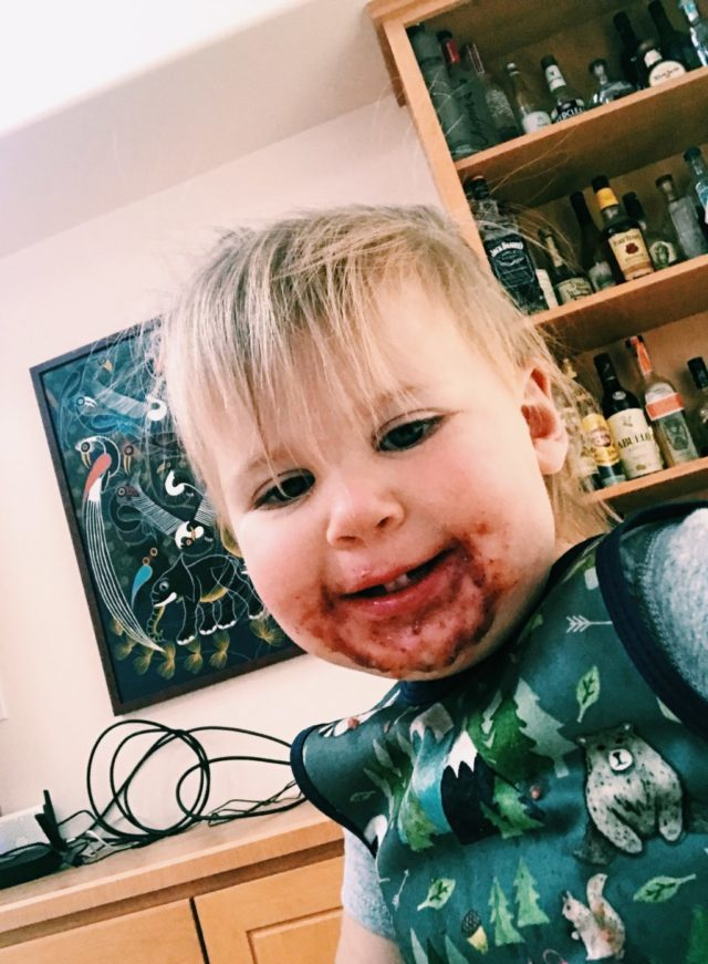A messy-faced toddler smiling after enjoying a smoothie bowl. Smoothie bowl are a great part of meal prep!