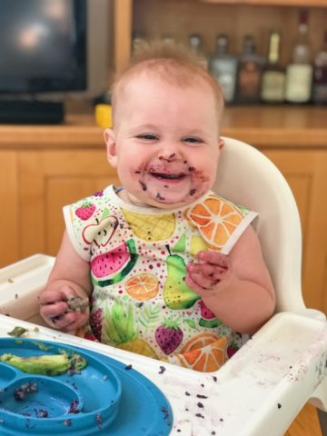 A cute baby eating some of her first solid foods (and getting them all over her face) in her highchair.