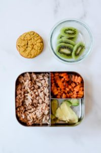 A packed toddler lunch consisting of ground turkey, butternut squash zig zags, avocado, and sliced kiwi, with a healthy pumpkin muffin for snack.