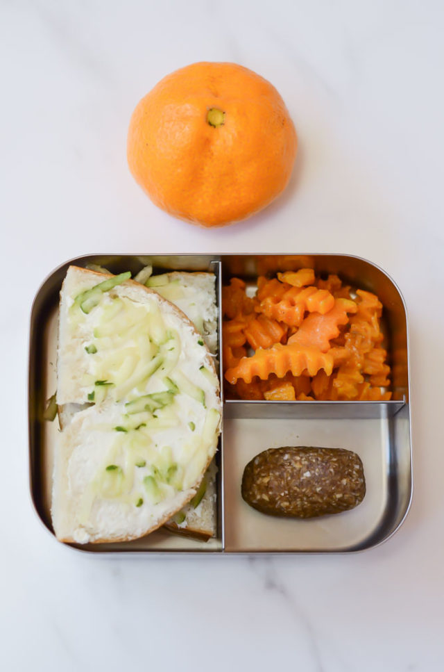 A packed toddler lunch consisting of half a bagel with cream cheese and shredded zucchini, butternut squash zig zags and a power protein bite, with an orange for dessert.