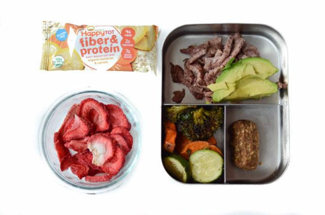 A packed toddler lunch consisting of sliced steak and avocado, roasted vegetables, a power protein bite and dehydrated strawberries for dessert. There's also a fiber and protein bar for snack!