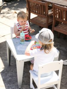 Two toddlers enjoying an outdoor lunch at a kids' table.