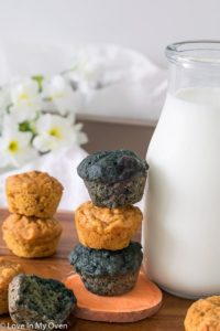 A stack of Mini Sweet Potato Muffins next to a glass carafe of milk. A perfect finger food for babies or toddlers!